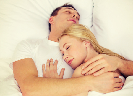 lovers in bed: hotel, travel, relationships, and happiness concept - happy couple sleeping in bed