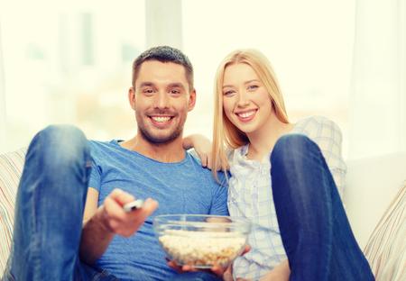 palomitas de maiz: comida, el amor, la familia y concepto de la felicidad - sonriente pareja con palomitas viendo cine en casa Foto de archivo