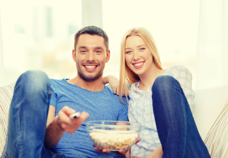 food, love, family and happiness concept - smiling couple with popcorn watching movie at home photo
