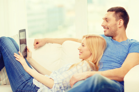 computer applications: love, family, technology, internet and happiness concept - smiling happy couple witl tablet pc computer at home