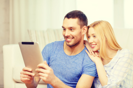 internet love: love, family, technology, internet and happiness concept - smiling happy couple witl tablet pc computer sitting on the floor at home