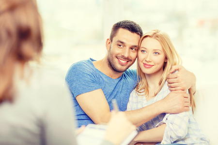 marriage counseling: love, family, phychology and happiness concept - young couple hugging at psychologist office