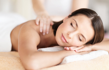 therapeutic massage: health, beauty, resort and relaxation concept - beautiful woman with closed eyes in spa salon getting massage