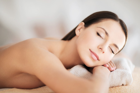 treatment: health and beauty, resort and relaxation concept - beautiful woman with closed eyes in spa salon lying on the massage desk