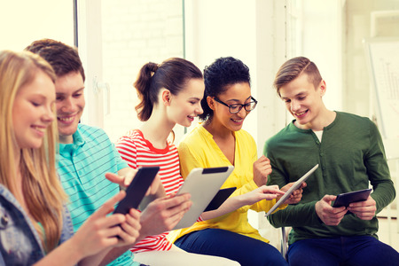 l'éducation, la technologie et internet concept - étudiants souriant regardant ordinateur tablette pc à l'école