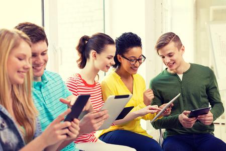 onderwijs, technologie en internet concept - lachende studenten kijken naar tablet-pc computer op school