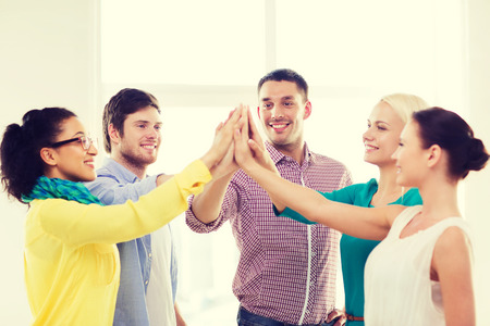 winning woman: business, office, gesture and startup concept - smiling creative team doing high five gesture in office