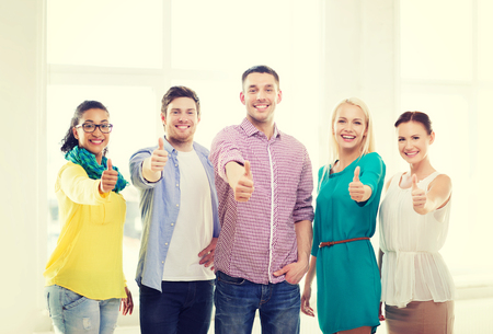 business, startup and office concept - happy creative team showing thumbs up in office photo