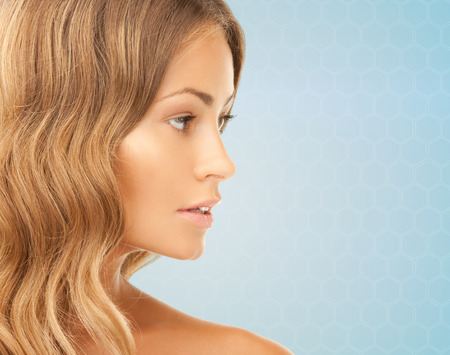 아름다움, 사람과 건강 개념 - 파란색 배경 위에 아름 다운 젊은 여자의 얼굴 스톡 콘텐츠