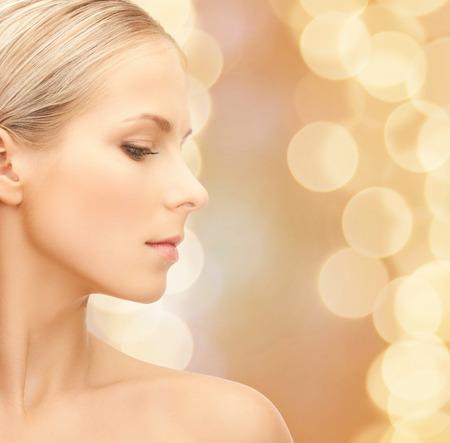 Schoonheid, mensen en gezondheid concept - mooie jonge vrouw gezicht over beige lichten achtergrond Stockfoto