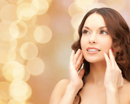 touching face: beauty, people and health concept - beautiful young woman touching her face over beige lights background Stock Photo