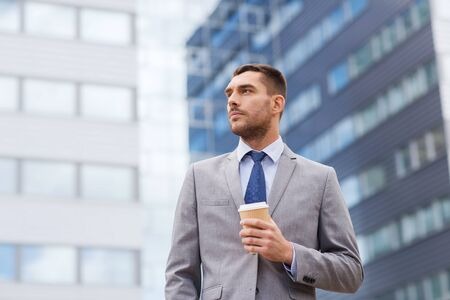 serious businessman: business, hot drinks and people and concept - young serious businessman with paper coffee cup over office building