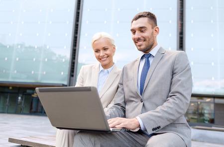 jovenes empresarios: negocios, la educaci�n, la tecnolog�a y la gente conceptuales - sonriente empresarios que trabajan con el ordenador port�til en la calle de la ciudad