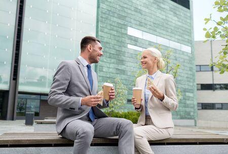 alimentos y bebidas: negocios, asociaci�n, alimentos, bebidas y concepto de la gente - hombres de negocios sonriente con los vasos de papel que se coloca sobre el edificio de oficinas Foto de archivo