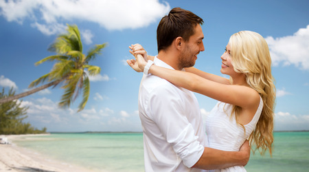 summer holidays, people, love, travel and dating concept - happy couple hugging over tropical beach background photo