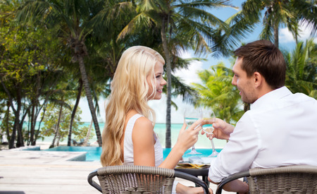 summer holidays, travel, tourism, celebration and dating concept - happy couple drinking wine in cafe over hotel beach with swimming pool background Stock Photo