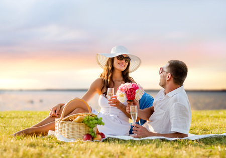 sea flowers: love, dating, people and holidays concept - smiling couple drinking champagne on picnic over evening seaside background