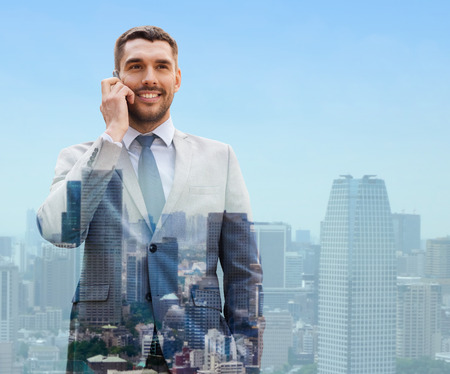 businessman talking: business, technology, communication and people concept - smiling businessman with smartphone talking over city background