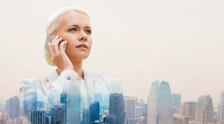 serious: business, technology, communication and people concept - serious businesswoman with smartphone talking over city background