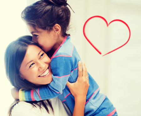 asian family home: family, children and happy people concept - hugging mother and daughter Stock Photo