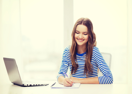 education, technology and home concept - smiling teenage girl with laptop computer, notebook and pen at home