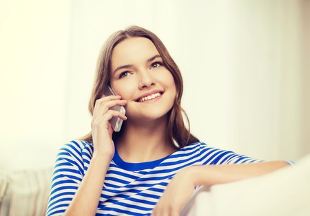 home, technology and communication concept - smiling teenage girl with smartphone sitting on couch at home photo