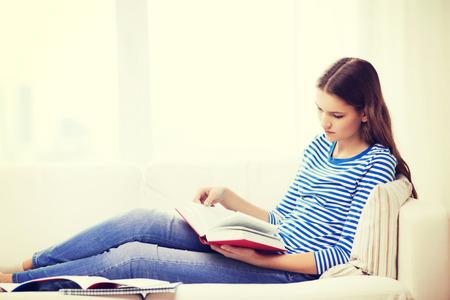 leasure: leasure e concetto di casa - calma adolescente donna lettura libro e seduto sul divano a casa