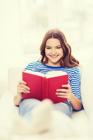 leasure: leasure e il concetto di casa - sorridente teenage ragazza leggendo il libro e seduto sul divano a casa