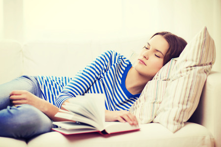 home and happiness concept - smiling teenage girl sleeping on sofa at home photo