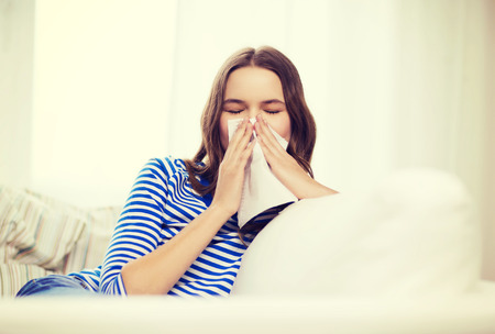 the sick: healthcare, medicine and home concept - sick teenage girl with paper tissue Stock Photo