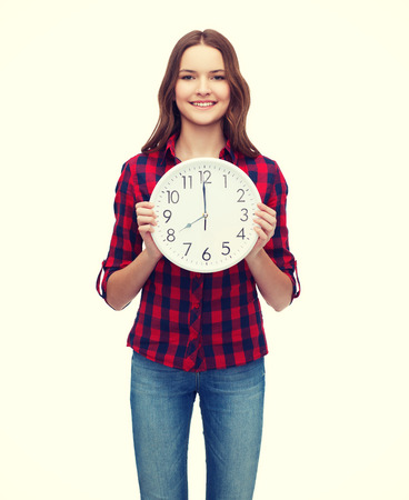 oclock: happiness and people concept - smiling young woman in casual clothes with wall clock showing 8 oclock