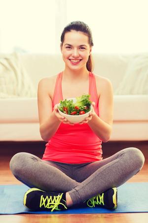 nice food: здравниц, диеты, дома и счастье понятие - улыбается спортивный девочка-подросток с зеленым салатом дома Фото со стока