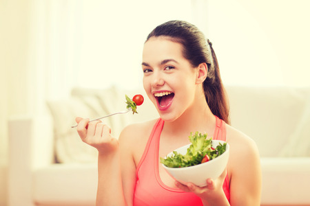 healt, dieting, home and happiness concept - smiling sporty teenage girl with green salad at home Archivio Fotografico