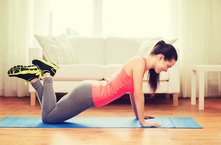 slender woman: fitness, home and diet concept - smiling teenage girl doing push-ups at home