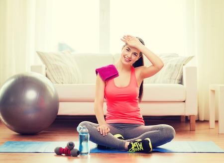 concepto de fitness, el hogar y la dieta - adolescente sonriente con la botella de agua después de hacer ejercicio en casa