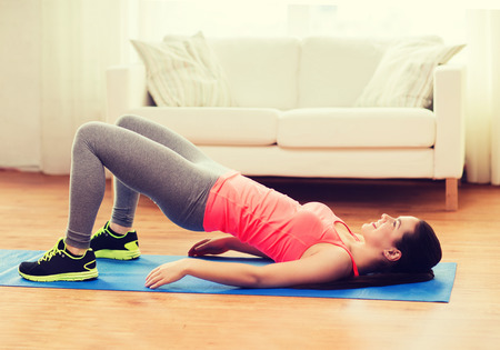 butt: fitness, home and diet concept - smiling teenage girl doing exercise for legs and buttocks on floor at home Stock Photo