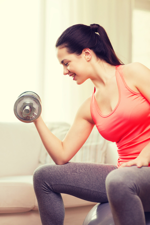 fitness, home and diet concept - smiling girl exercising with fitness ball and dumbbells at home photo