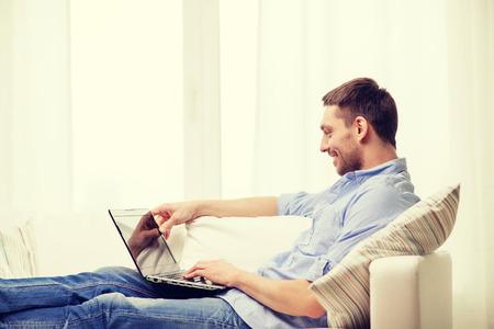 trabjando en casa: concepto de la tecnología, hogar y estilo de vida - sonriente hombre de trabajo con ordenador portátil en casa