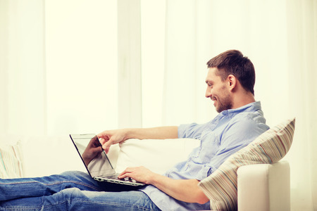 work from home: technology, home and lifestyle concept - smiling man working with laptop at home