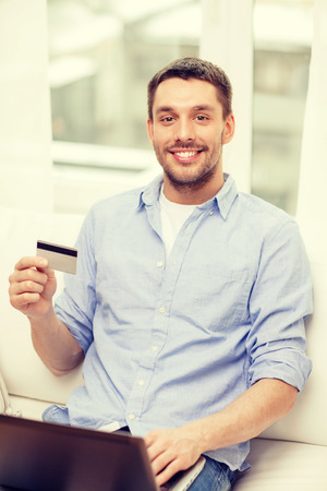 technology, home and lifestyle concept - smiling man working with laptop and credit card at home photo