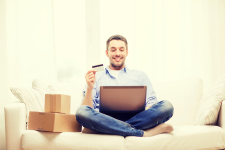 service card: technology, home and lifestyle concept - smiling man with laptop, credit card and cardboard boxes at home
