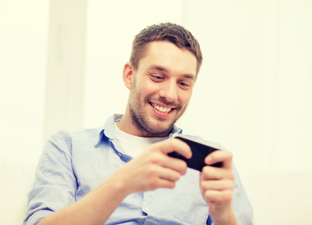 gamer: home, technology and internet concept - smiling man with smartphone sitting on couch at home