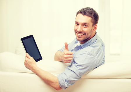 technology, home and lifestyle concept - smiling man working with tablet pc computer at home showing thumbs up photo