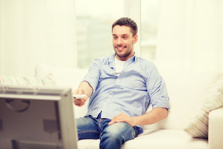 free time: home, technology and entretainment concept - smiling man with tv remote control at home