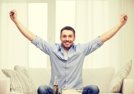 sport fan: sports, happiness and people concept - smiling man watching sports on tv and supporting team at home Stock Photo