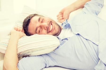 自宅のソファーに横になっている若い男の笑みを浮かべて - 家と幸福の概念