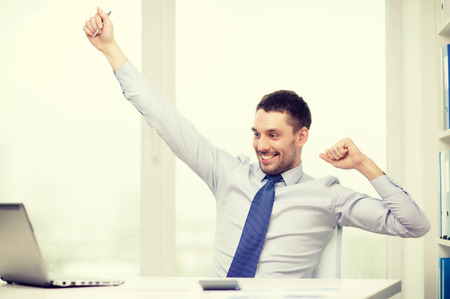 raised hands: office, business, technology, finances and internet concept - smiling businessman with laptop computer and documents at office