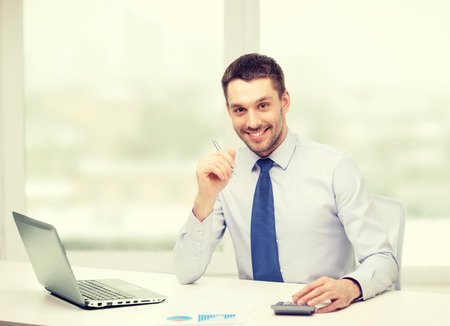 office, business, technology, finances and internet concept - smiling businessman with laptop computer and documents at office photo
