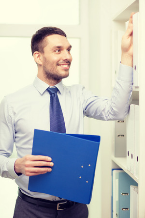 business and office concept - handsome businessman holding folder and picking another one at office photo