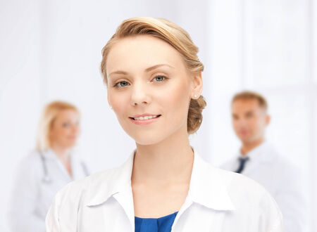 medicine, people, profession and teamwork concept - smiling young female doctor over group of medics in hospital photo